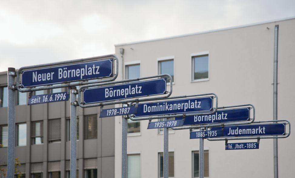 Eine Fotografie zeigt Straßenschilder mit den verschiedenen Namen des Börneplatzes von 1885 bis heute