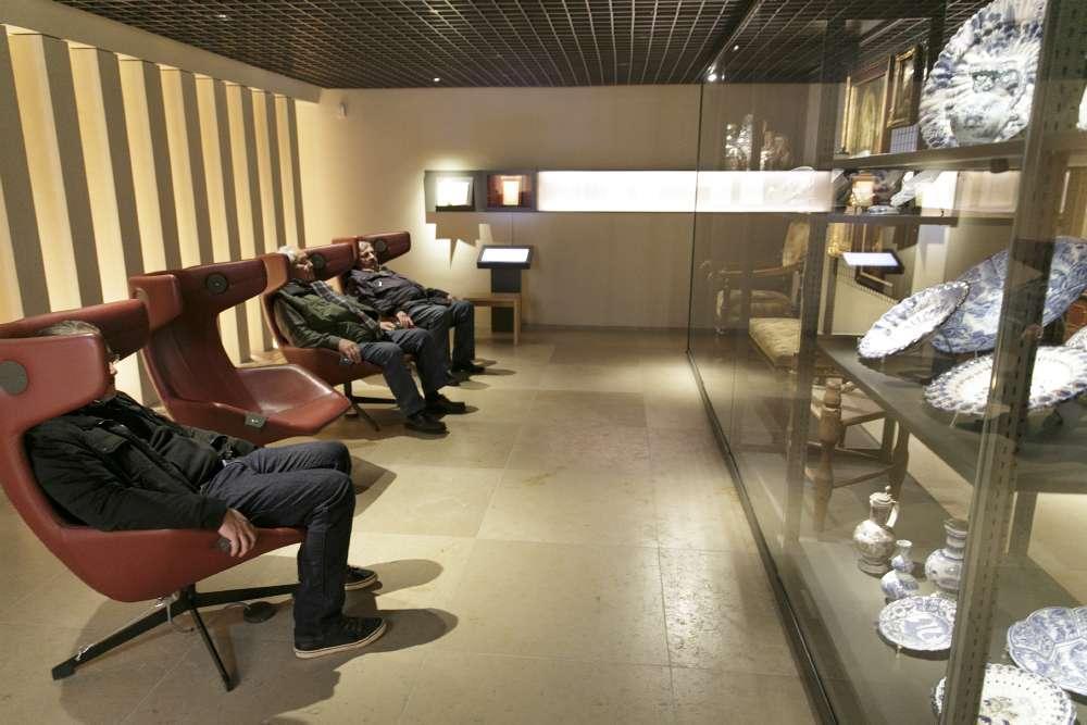 Besucher der Sammlung Heyman sitzen in Multimediasesseln