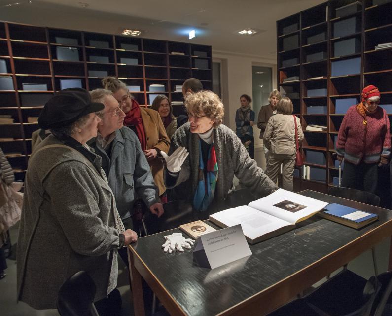 Ein Foto zeigt Besucher, die sich angeregt in der Bibliothek der Alten unterhalten