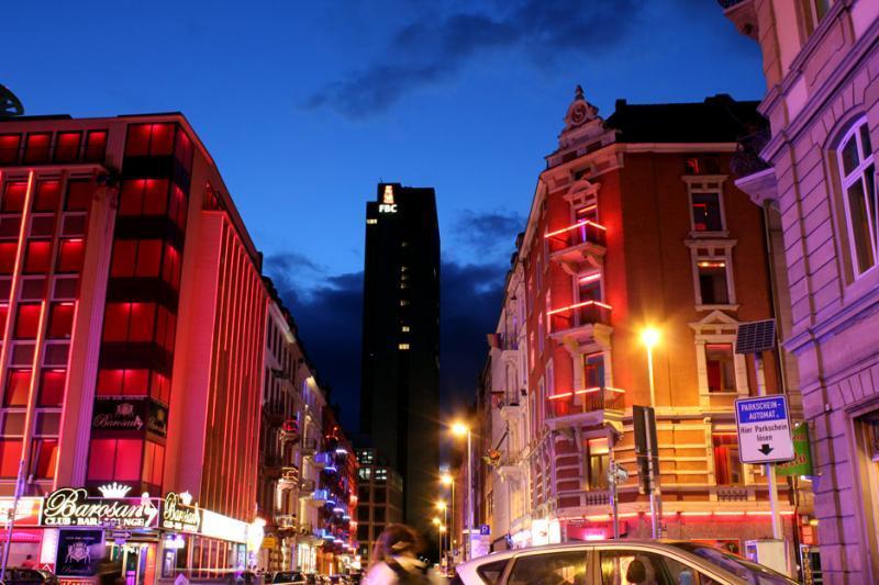 Blick in die Elbestraße bei Nacht, im Vordergrund Rotlichtviertel, im Hintergrund ein Hochhaus