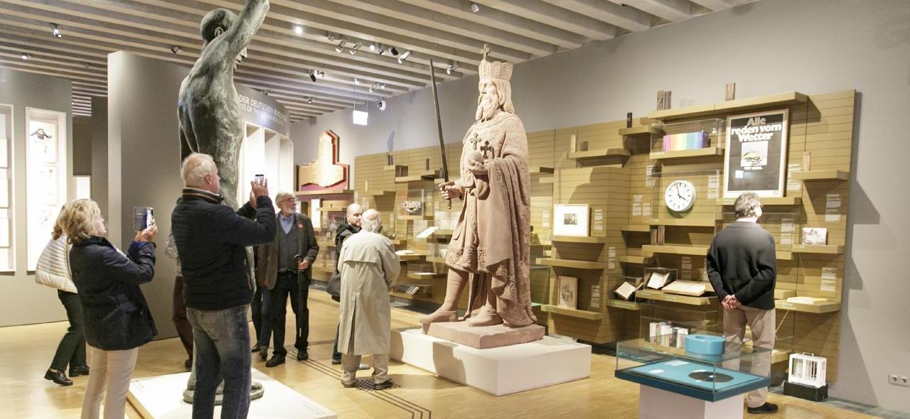 Auf dem Bild sind Besucher/innen im Museum zu sehen, die Fotos von der Statue Kaiser Karls machen