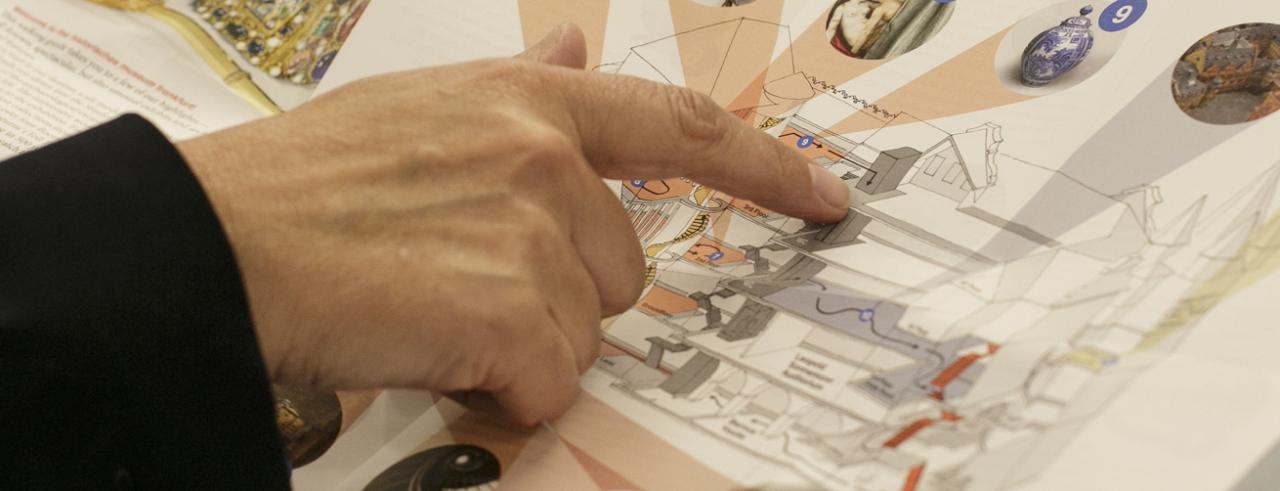 Eine Hand zeigt auf einen Lageplan des Museums
